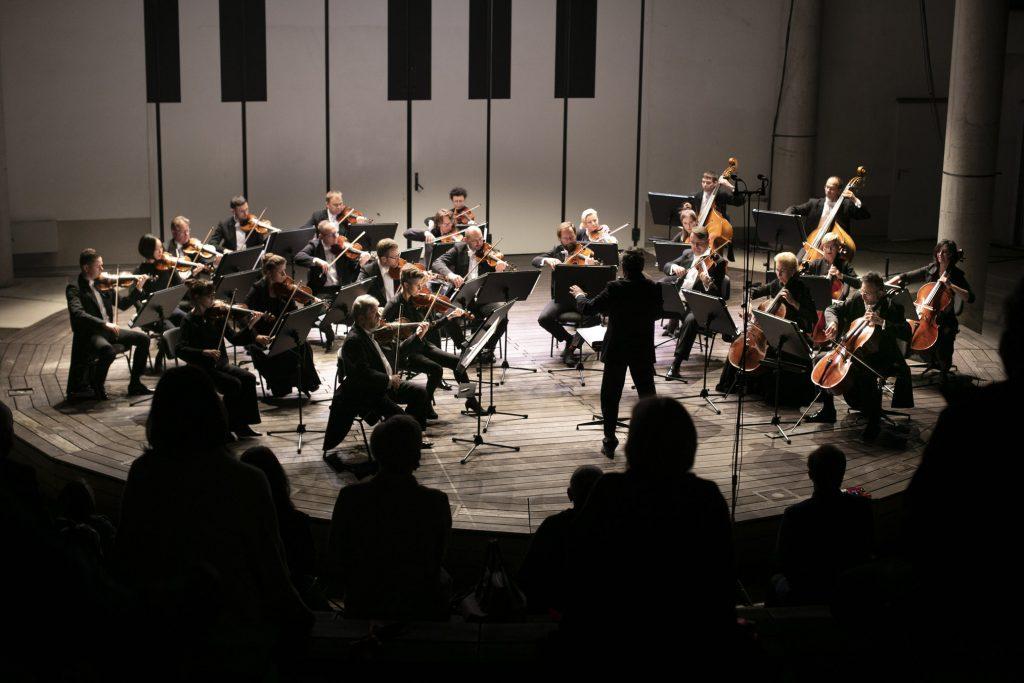 Koncert wieczorny w amfiteatrze. Na scenie kwintet smyczkowy Opery i Filharmonii Podlaskiej wraz z dyrygentem.