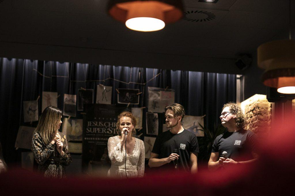 Czwórka wykonawców musicalu ''Jesus Christ Superstar'' , dwie kobiety i dwóch mężczyzn w czarnych koszulkach z napisem ''Jesus Christ Superstar''stoi obok siebie z mikrofonami. Jedna z kobiet mówi do mikrofonu. Pozostałe osoby są zwrócone w jej kierunku. Za nimi kotara, na niej przyczepione rysunki , na środku duży plakat promujący musical ''Jesus Christ Superstar.''