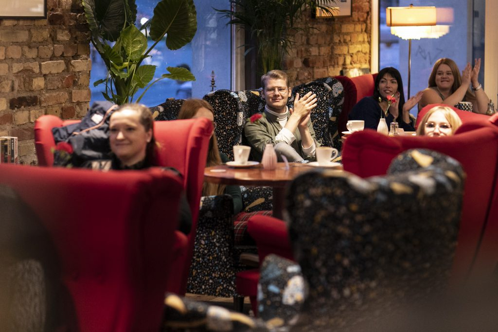 Kilka osób siedzi przy stolikach w czerwonych fotelach. Wszyscy patrzą w jedną stronę. Część z nich bije brawo.