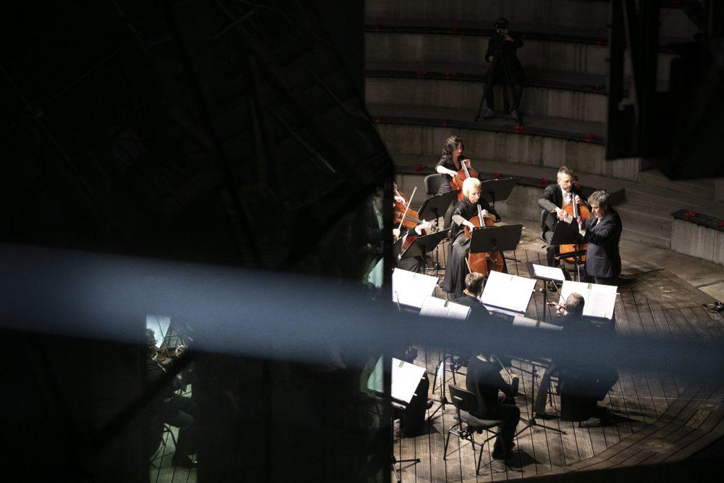 Koncert wieczorny na scenie letniej Opery i Filharmonii Podlaskiej. Z przodu kilku muzyków orkiestry kameralnej , przed nimi dyrygent.