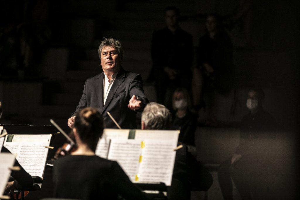 Koncert wieczorny na scenie letniej Opery i Filharmonii Podlaskiej. Z przodu kilku muzyków orkiestry kameralnej , przed nimi dyrygent. W oddali, w półmroku publiczność.