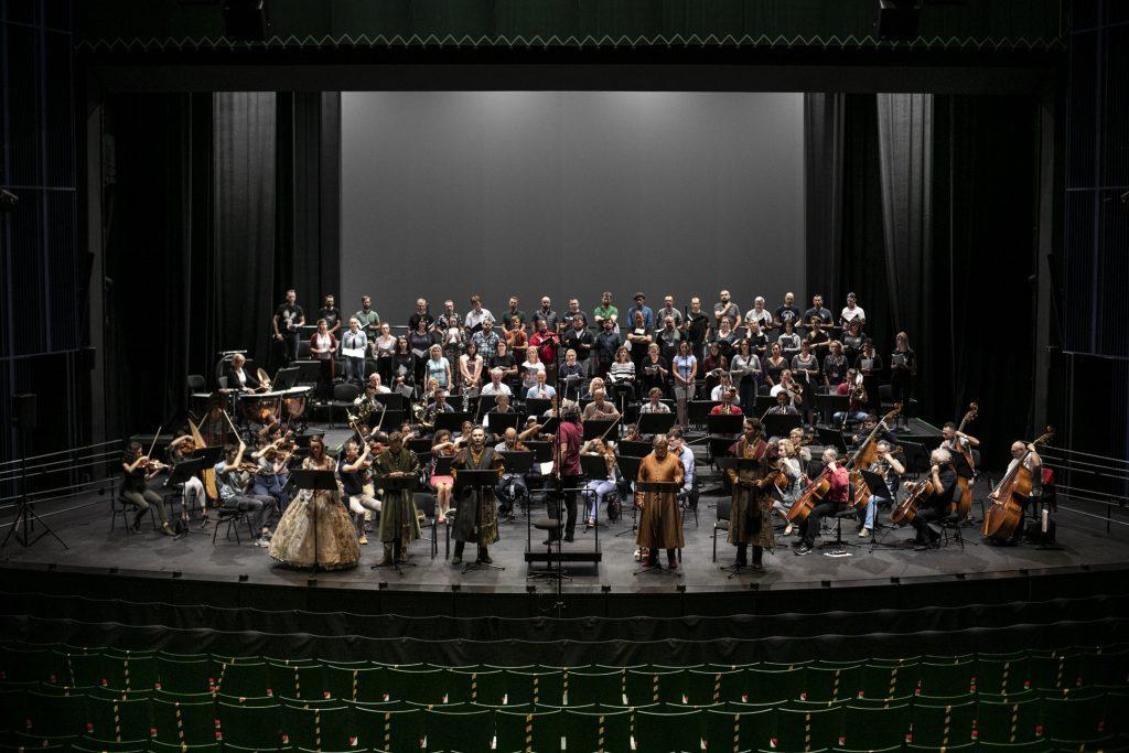 Próba do koncertu. Z przodu część pustej widowni. Na scenie przy pulpitach stoją soliści. Na środku stoi dyrygent. Dalej siedzi orkiestra, za nimi chór.