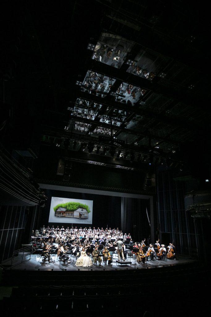 Widok na scenę z końca sali. Widownia w półmroku. Na oświetlonej scenie soliści , chór i orkiestra podczas próby do koncertu. Za nimi duży bilbord promujący koncert ''Verbum Nobile''