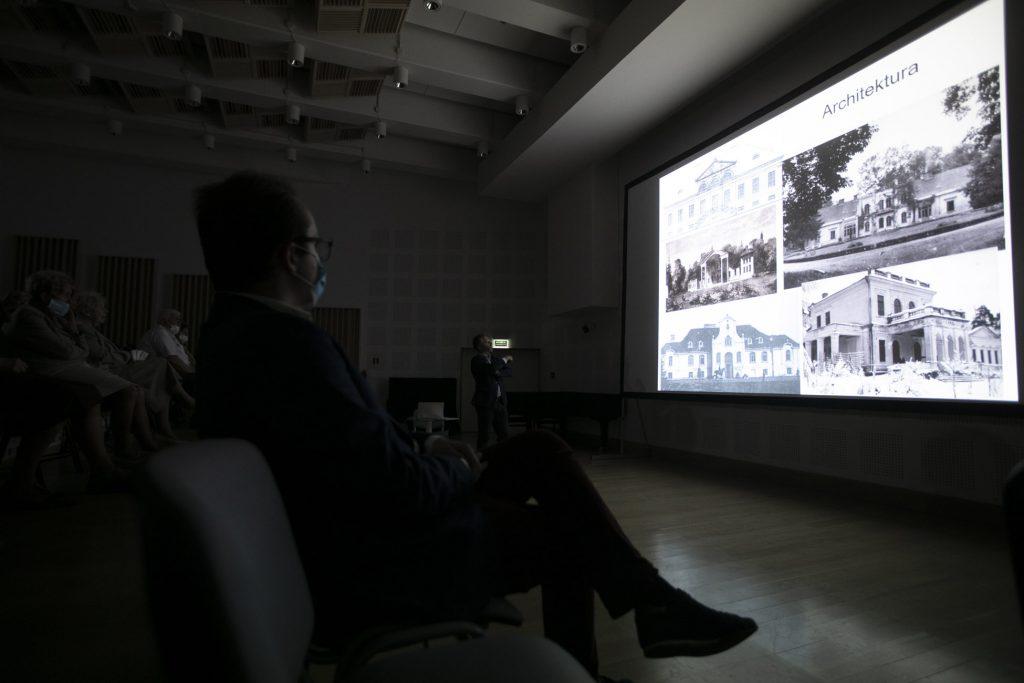Ciemna sala. Po prawej stronie ekran na którym wyświetlone są czarno-białe zdjęcia dworów polskich. Przed ekranem , po lewej stronie siedzą widzowie w maseczkach ochronnych.