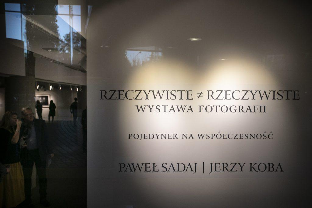 Na zdjęciu plakat informujący o wystawie fotografii która nosi tytuł : Rzeczywiste # Rzeczywiste , Pojedynek na współczesność. Paweł Sadaj Jerzy Koba.