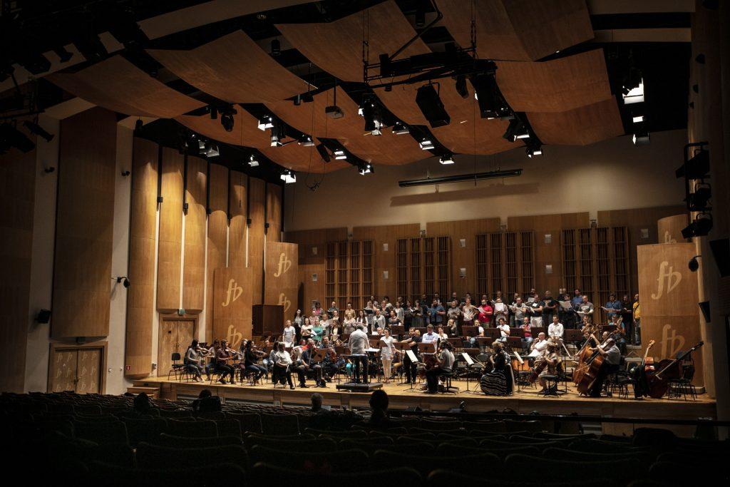 Zdjęcie zrobione z końca widowni. W oddali scena. Na niej kilkadziesiąt osób, soliści, muzycy i chórzyści podczas próby. Z przodu dyrygent.