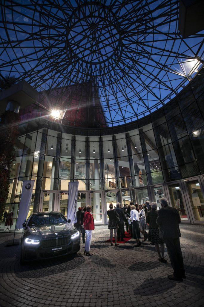 Przed wejściem do gmachu Opery stoją przybyli goście. Po lewej stronie samochód marki ''BMW''.