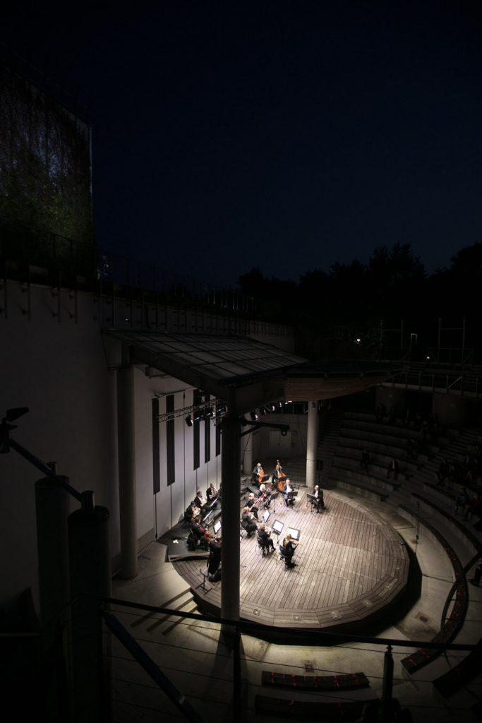 Zdjęcie zrobione z góry. Na scenie amfiteatru kwintet smyczkowy przed koncertem wieczornym. Scena oświetlona, dookoła półmrok.
