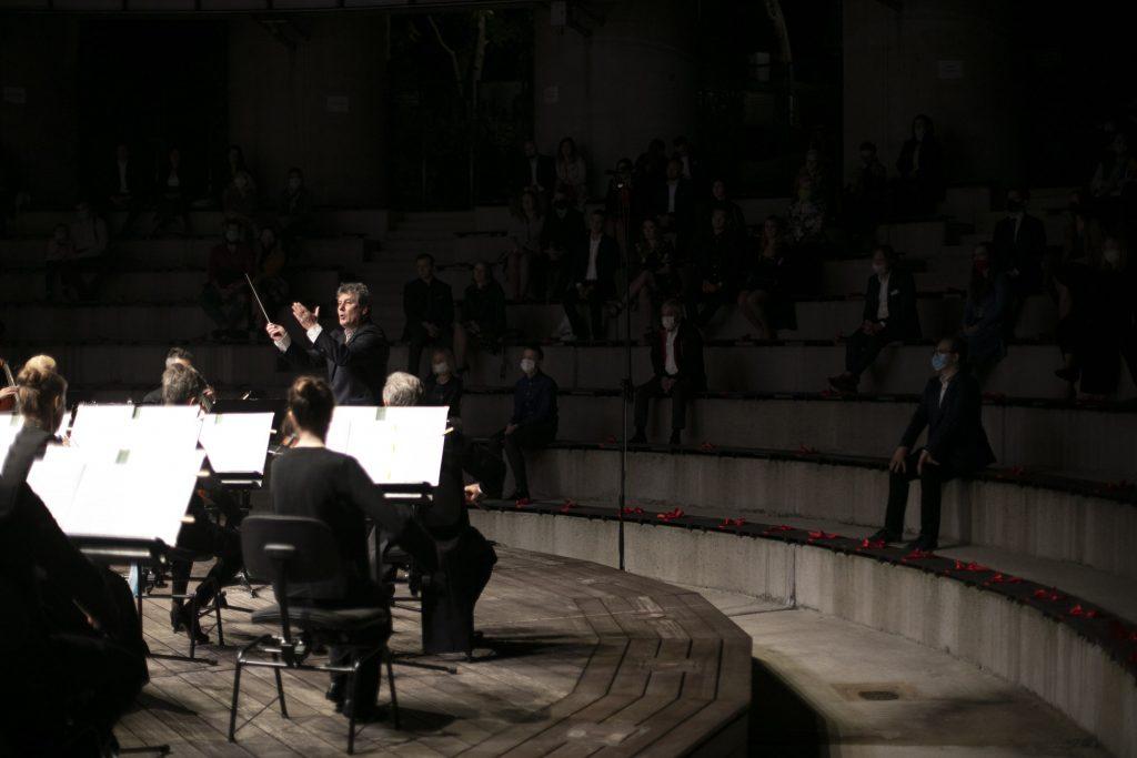 Po lewej stronie scena amfiteatru Opery. Na niej orkiestra kameralna. Przed nimi dyrygent. Po prawej stronie widownia w półmroku.