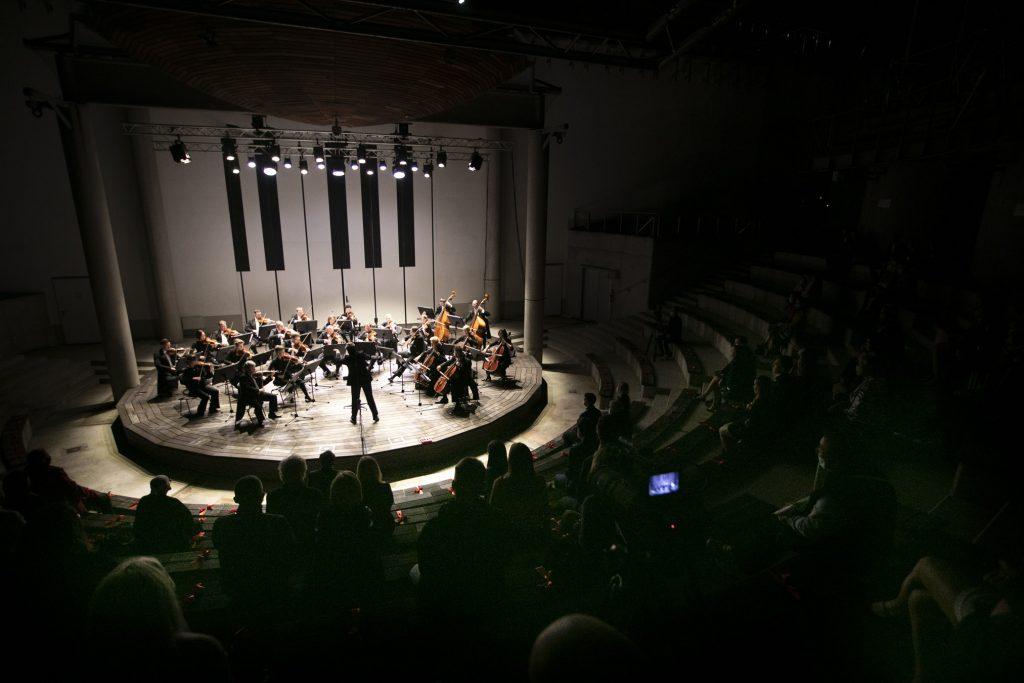 Koncert wieczorny w amfiteatrze. Na scenie orkiestra kameralna Opery i Filharmonii Podlaskiej. Widownia w półmroku.