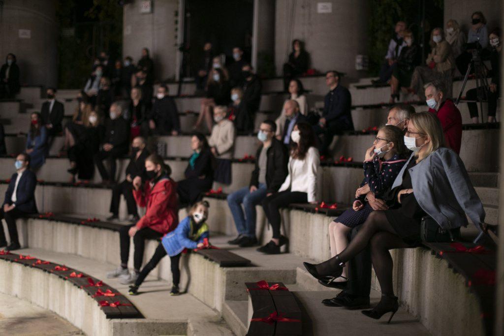 Publiczność siedząca na widowni amfiteatru podczas wieczornego koncertu. Wszyscy maja na twarzach maseczki ochronne.