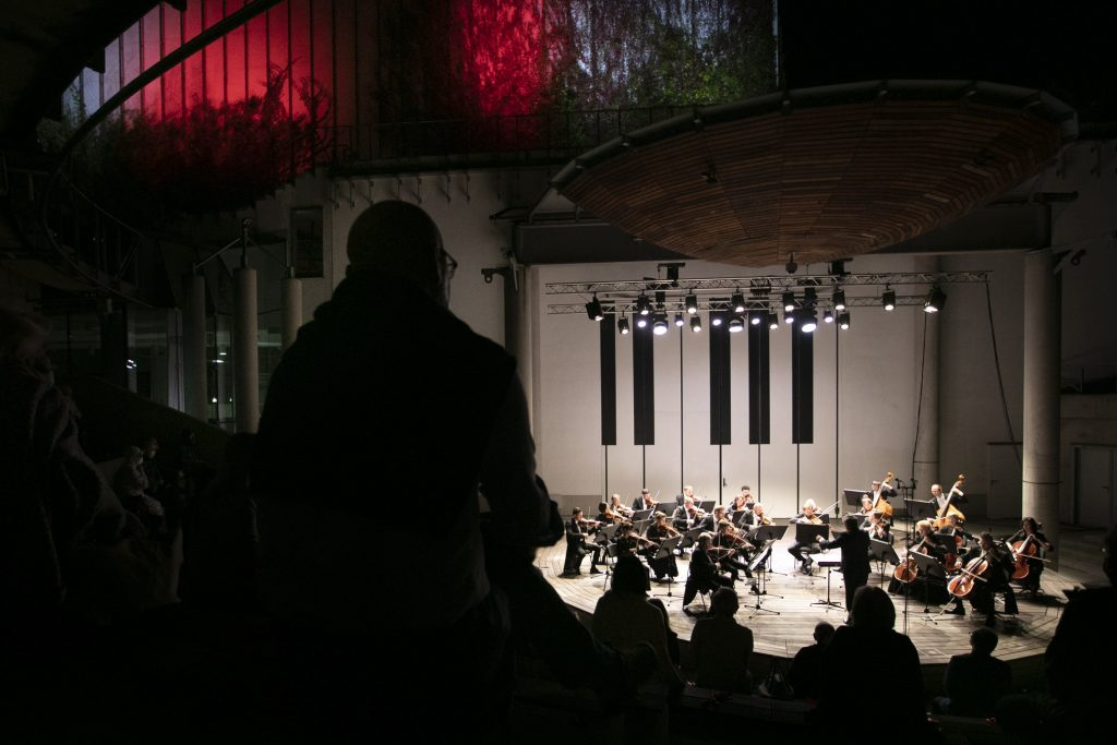 Wieczorny koncert w amfiteatrze Opery I Filharmonii Podlaskiej. Na oświetlonej scenie kwintet smyczkowy. Widownia w półmroku.