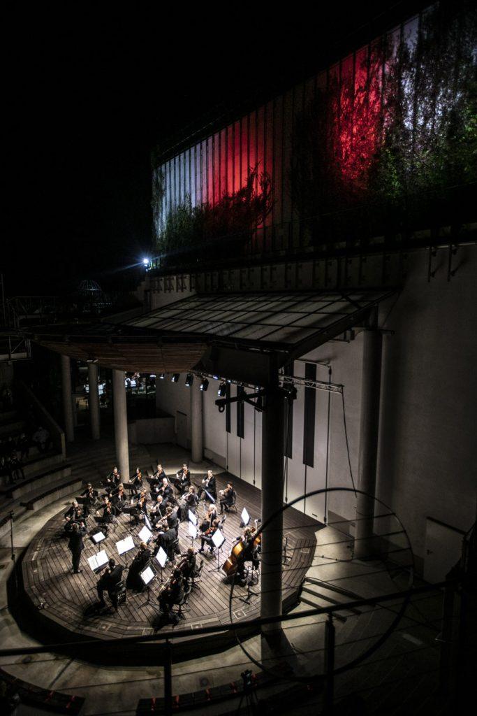 Koncert wieczorny w amfiteatrze. Podświetlona scena ujęta z góry. Na scenie kwintet smyczkowy. Budynek Opery Podświetlony na biało-czerwono.