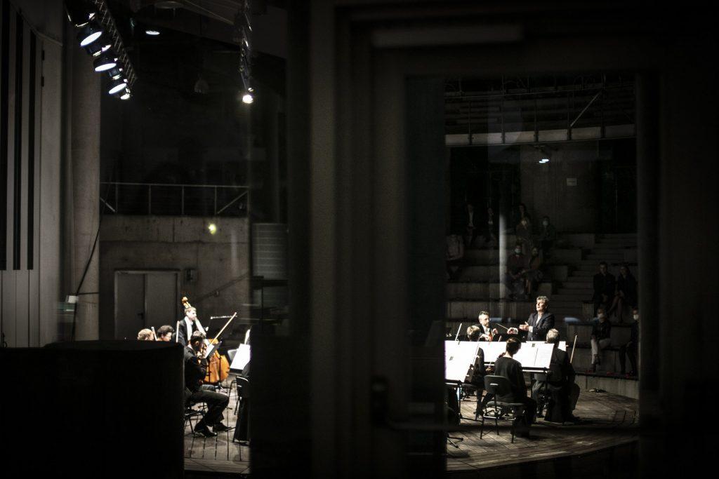 Scena amfiteatru ujęta zza filara. Na scenie orkiestra kameralna podczas wieczornego koncertu.