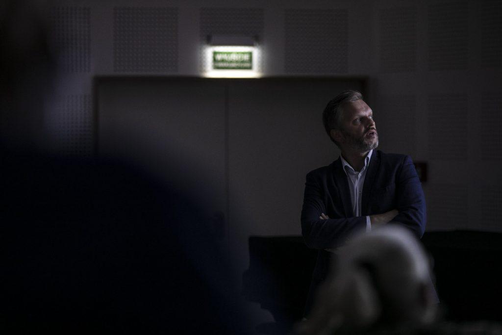 Mężczyzna z założonymi rękami w słabo oświetlonej sali patrzy w lewo.