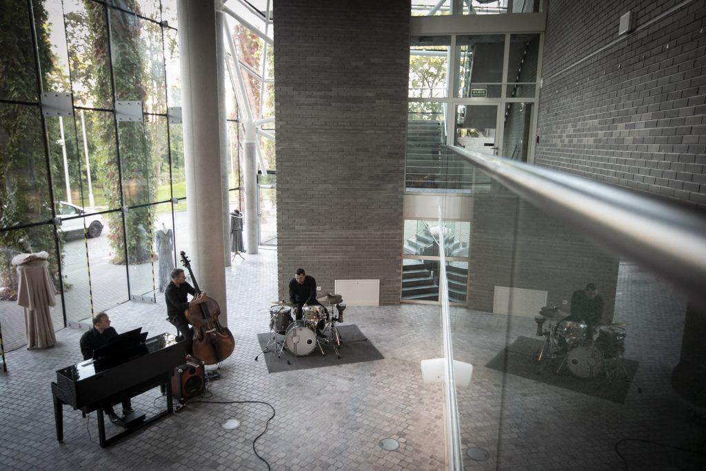 Zdjęcie zrobione z góry. Na dolnym foyer trzech mężczyzn przy instrumentach muzycznych, perkusji, kontrabasie i pianino.
