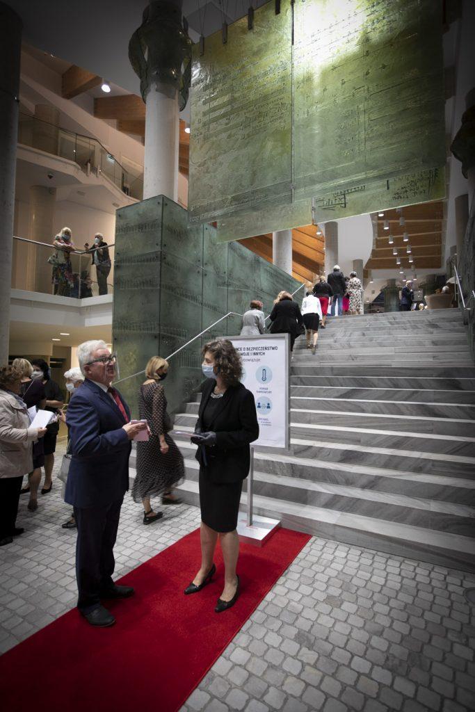 Przy głównych schodach rozłożony jest czerwony dywan. Na środku, w ciemnym kostiumie, w maseczce ochronnej i rękawiczkach i stoi Dyrektor Opery i Filharmonii Podlaskiej - Ewa Iżykowska-Lipińska. Wokół goście, którzy przybyli na Koncert Inauguracyjny.
