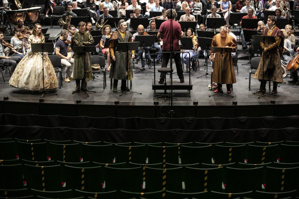 Próba do koncertu. Z przodu kilka rzędów widowni. Część krzeseł zabezpieczone taśmą. Na scenie z przodu stoją soliści. Pomiędzy nimi na podeście stoi dyrygent. Dalej siedzi orkiestra.