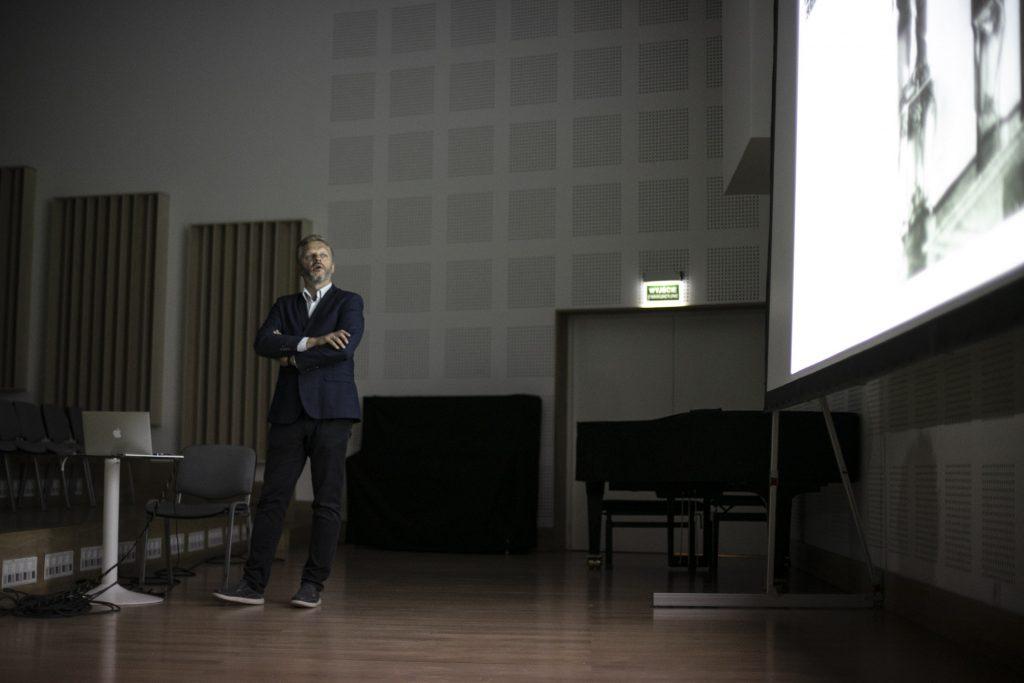 Po lewej stronie stoi mężczyzna w ciemnej marynarce z założonymi rękami. Przed nim na stoliku rozłożony laptop. Patrzy na ekran po prawej stronie.