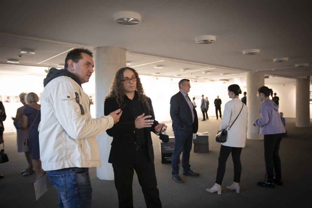 Sala wystawowa. Po lewej stronie stoi dwóch mężczyzn rozmawiając ze sobą. Wokół widać ludzi stojących w grupach.