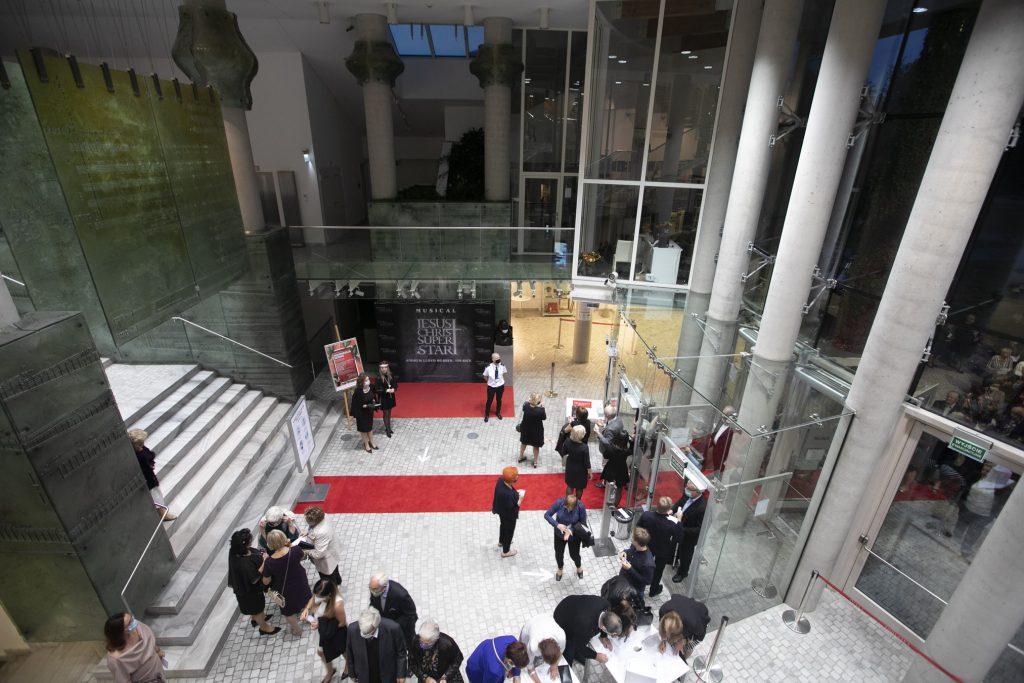 Zdjęcie z góry. Wejście do gmachu Opery i Filharmonii Podlaskiej. Wzdłuż wejścia leży czerwony dywan. Na dolnym foyer pracownicy i goście którzy przybyli na Koncert Inauguracyjny.