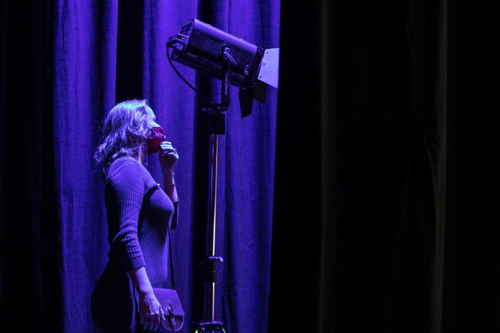 Na tle czarnej kotary, oświetlonej na niebiesko stoi kobieta. Na twarzy ma założoną maseczkę ochronną. Koło niej stoi reflektor na statywie.
