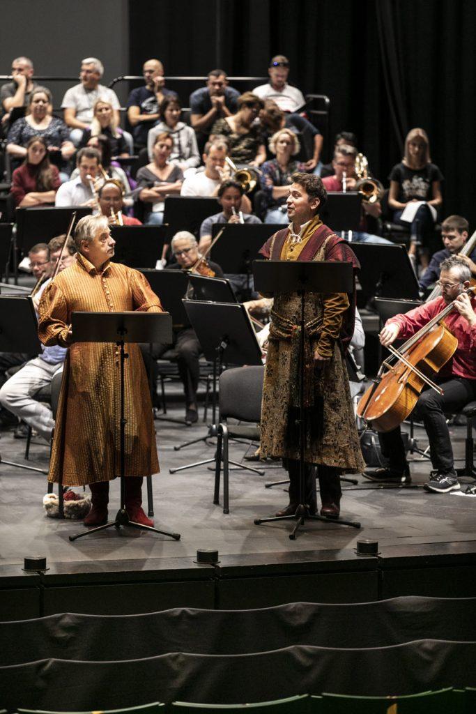Na scenie przy pulpitach stoi dwóch solistów w strojach szlacheckich. Za nimi gra orkiestra. Na końcu siedzi chór.