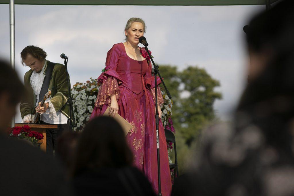 Dwoje artystów na scenie w kostiumach z epoki. Kobieta w czerwonej sukni stoi przed mikrofonem, po lewej mężczyzna gra na gitarze.