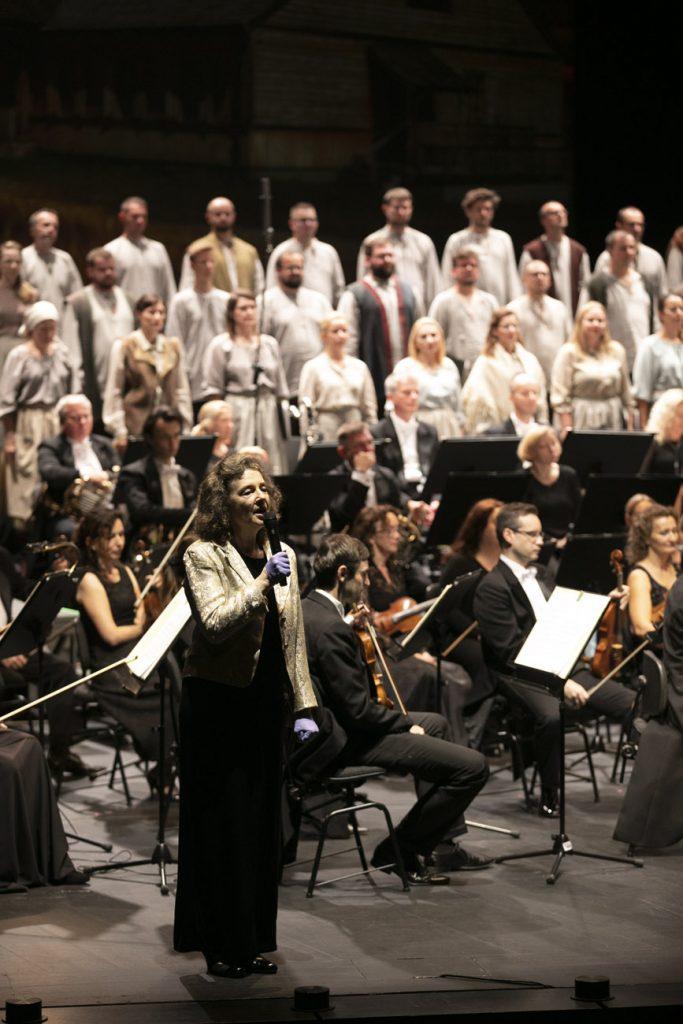Na scenie Dyrektor Opery i Filharmonii Podlaskiej Prof. Ewa Iżykowska - Lipińska mówi do mikrofonu. Za nią siedzi orkiestra. Dalej stoi chór w białych kostiumach.