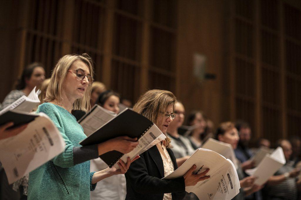 Kilkunastu chórzystów stoi z rozłożonymi teczkami podczas próby do koncertu.