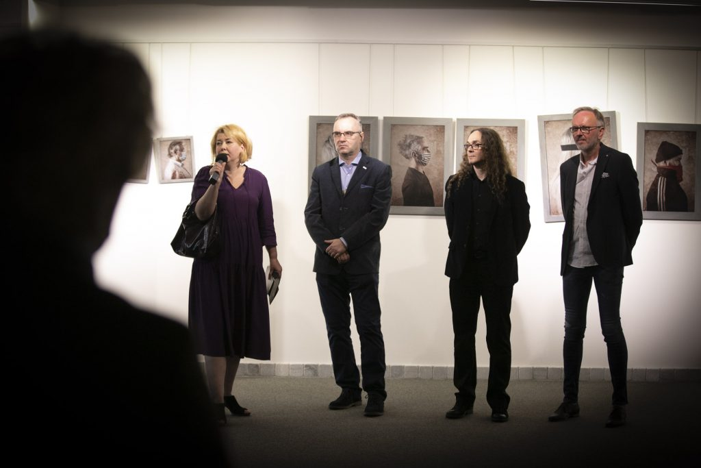 Cztery osoby stoją przed ścianą na której wiszą fotografie. Jedna kobieta, która mówi trzymając mikrofon i trzech mężczyzn stojących obok.