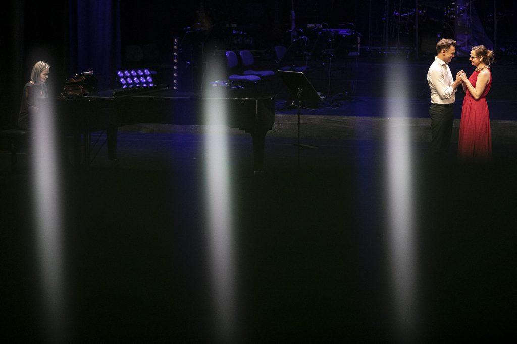 Po prawej stronie stoją kobieta i mężczyzna, trzymając się za ręce. Po lewej przy fortepianie siedzi kobieta. Scena oświetlona na niebiesko.