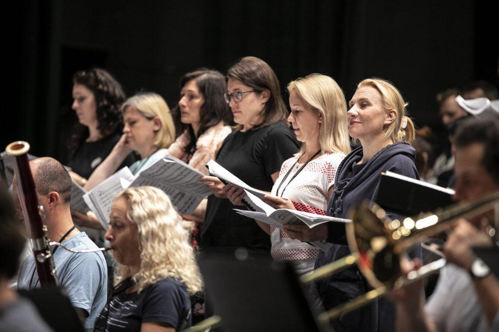 Próba do koncertu. Kilka chórzystek stoi z otwartymi nutami. Przed nimi gra kilku muzyków z orkiestry.