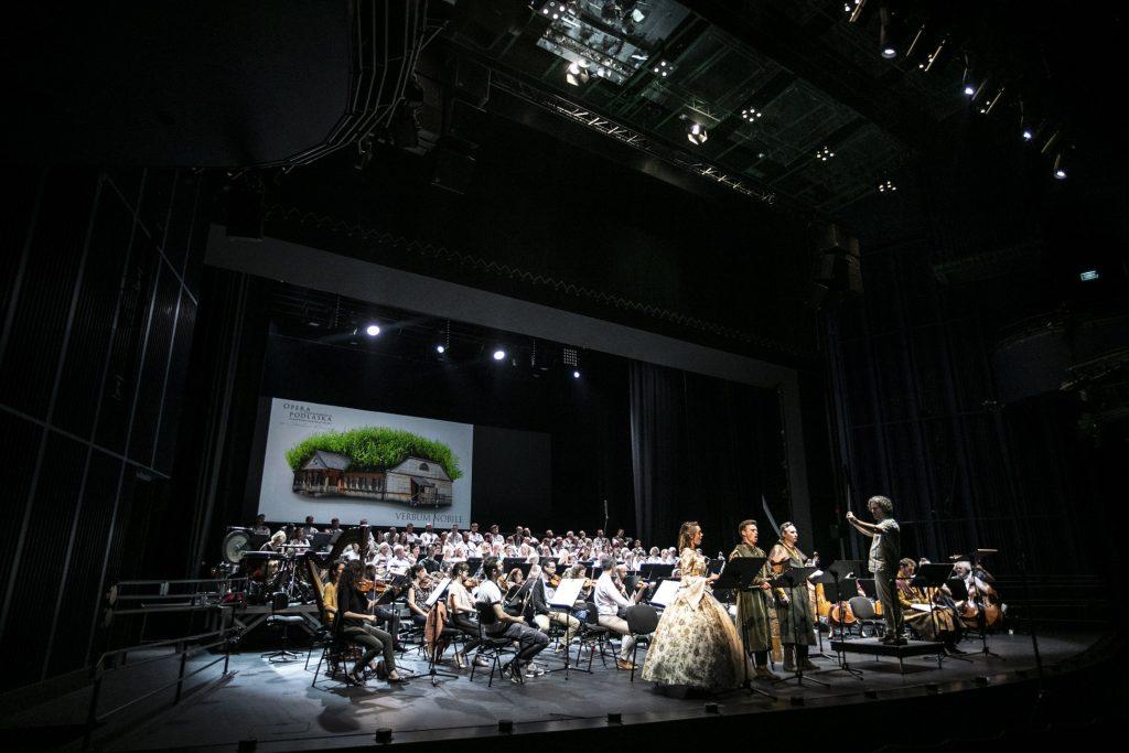 Widok na scenę z boku. Z przodu sceny stoi troje solistów, kobieta w jasnej sukni i dwóch mężczyzn w strojach szlacheckich. Obok, na podeście stoi z uniesionymi rękoma dyrygent. Przed dyrygentem siedzi orkiestra, za nimi chór. W tle duży bilbord ''Verbum Nobile''.