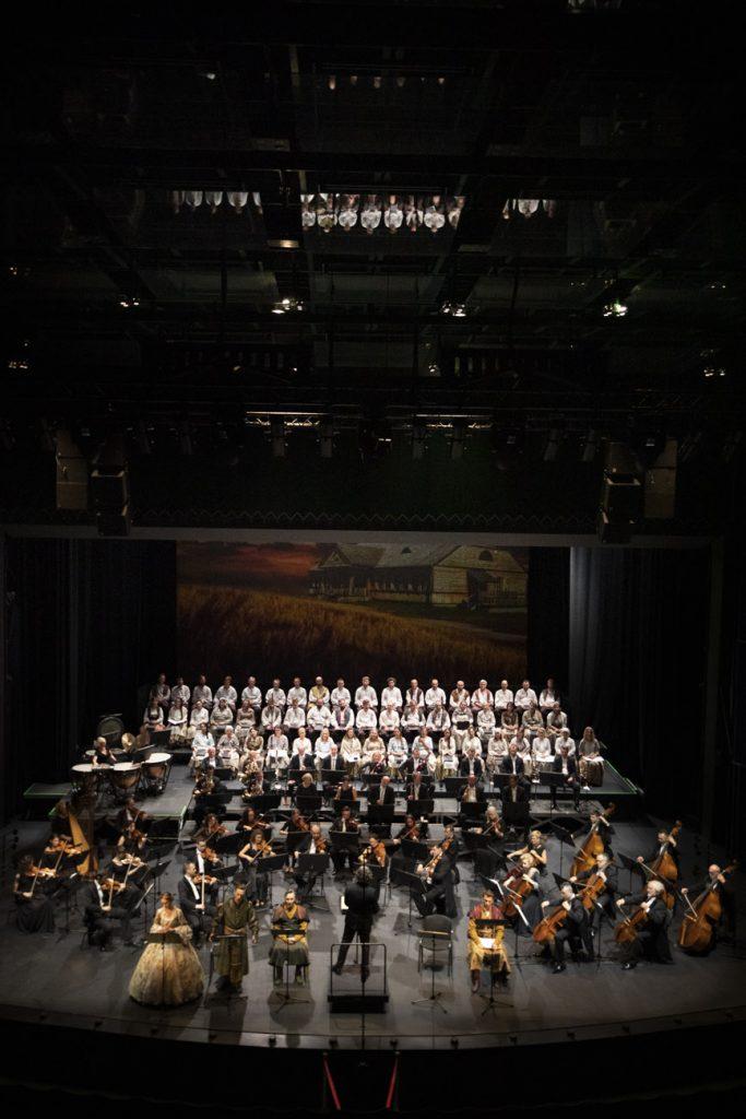 Widok sceny z góry. Z przodu soliści w kostiumach i dyrygent. Za nimi orkiestra. Na końcu sceny chór w białych kostiumach.