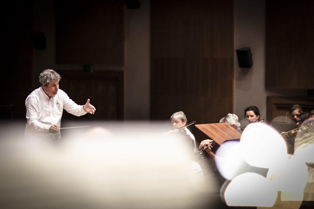 Po lewej stronie dyrygent, w ręku trzyma batutę. Przed nim orkiestra podczas próby.