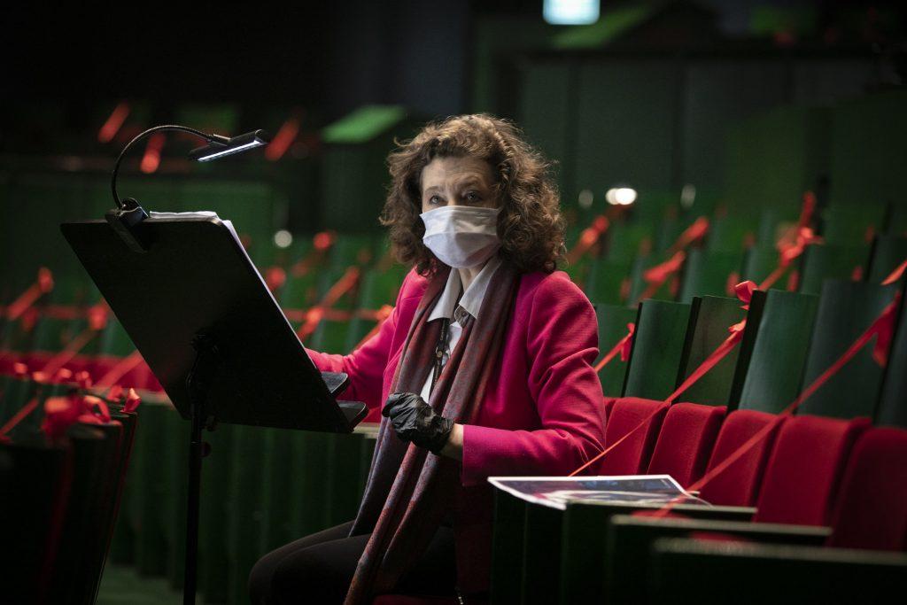 Widownia Opery częściowo zabezpieczona czerwonymi wstążkami. Na jednym z foteli, w maseczce ochronnej i rękawiczkach, siedzi Dyrektor Instytucji. Przed nią pulpit na nuty.