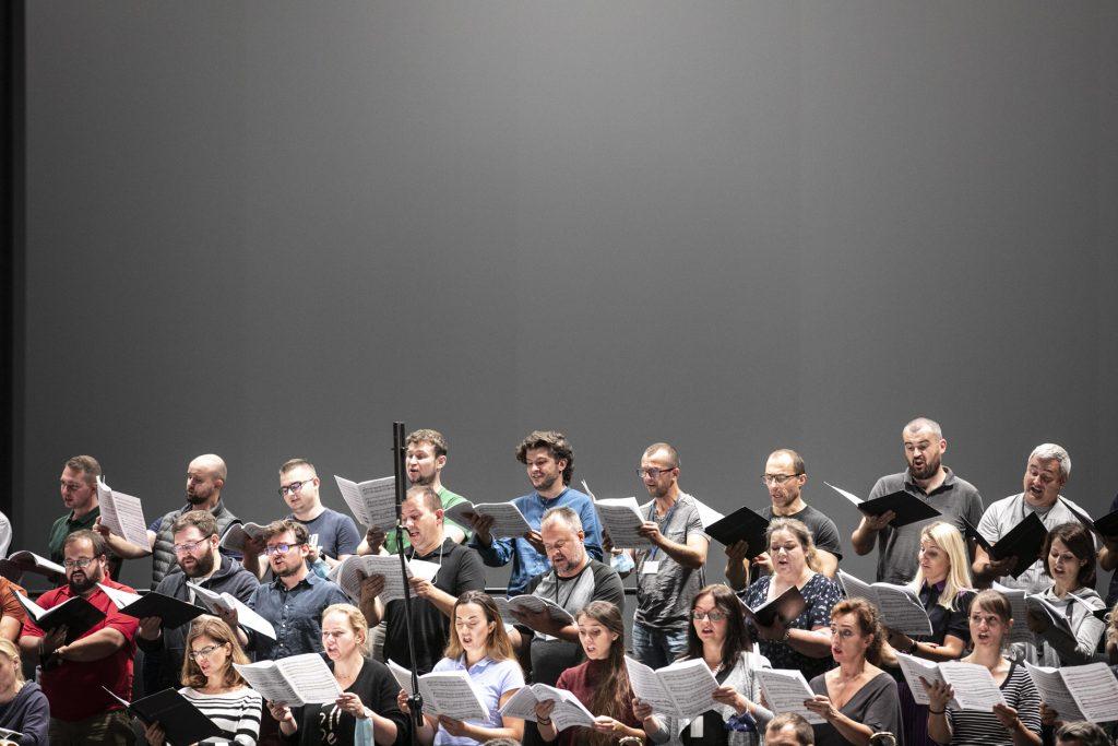 Próba do koncertu. Zbliżenie na chór opery stojący w kilku rzędach. Wszyscy trzymają otwarte nuty.