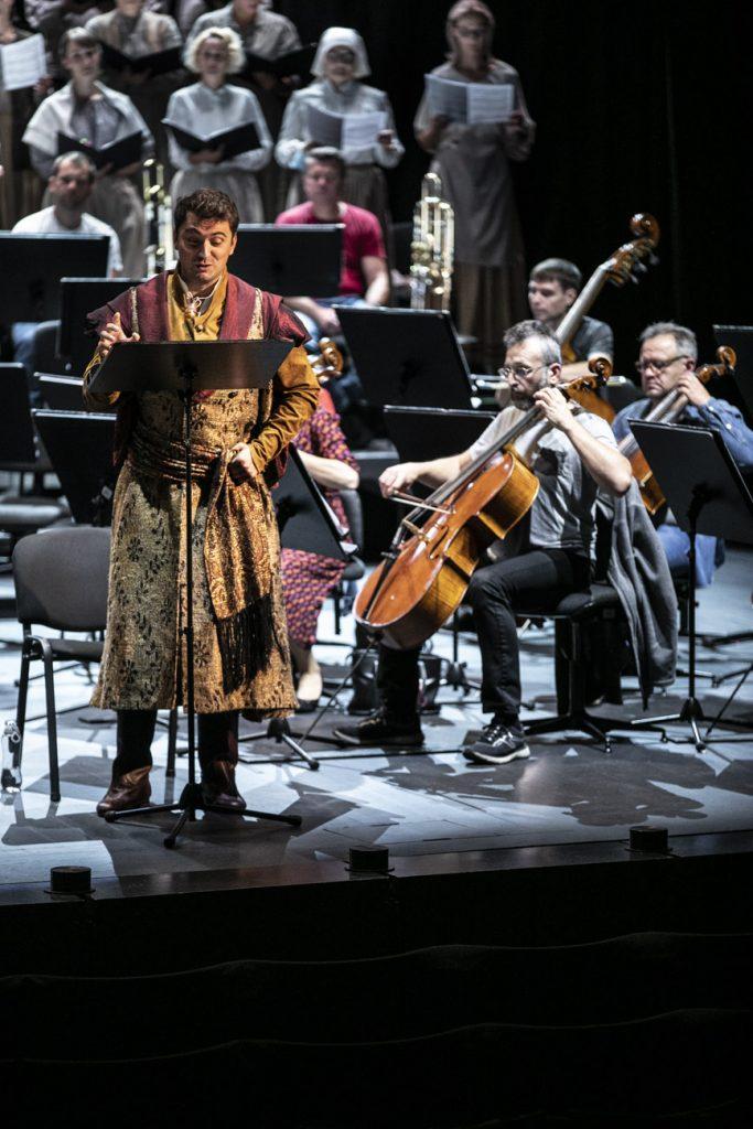 Na scenie, przed pulpitem stoi solista w stroju szlacheckim. Za nim gra grupa wiolonczel. W tle stoją artyści części chóru z rozłożonymi nutami.