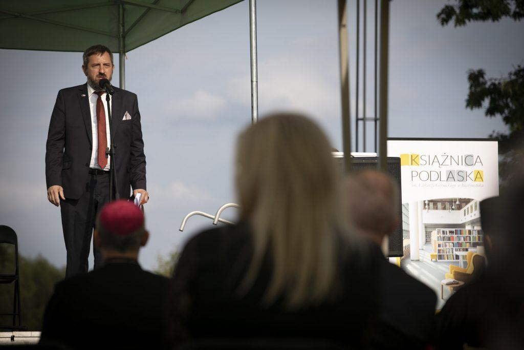 Po lewej stronie burmistrz Supraśla stoi przed mikrofonem , po prawej plakat reklamowy Książnicy Podlaskiej.