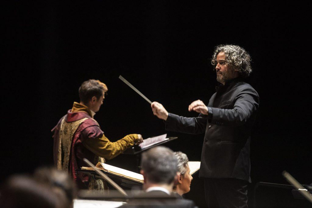 Po prawej stronie, bokiem stoi dyrygent z uniesionymi rękami. W prawej ręce trzyma batutę. Obok stoi solista w stroju szlacheckim odwrócony plecami. Przed nim pulpit z rozłożonymi nutami.