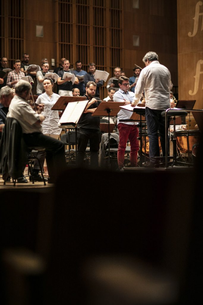 Na podeście stoi dyrygent, za nim soliści, muzycy i chórzyści podczas próby do koncertu.