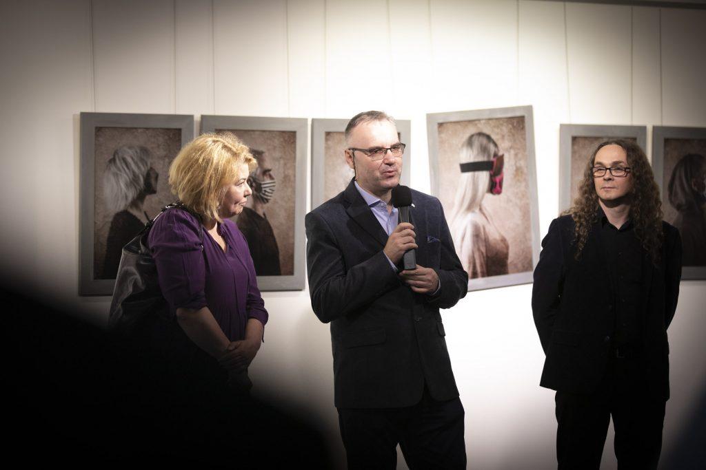 Przy ścianie na której wiszą fotografie stoi dwóch mężczyzn i jedna kobieta. Jeden z mężczyzn trzyma mikrofon.
