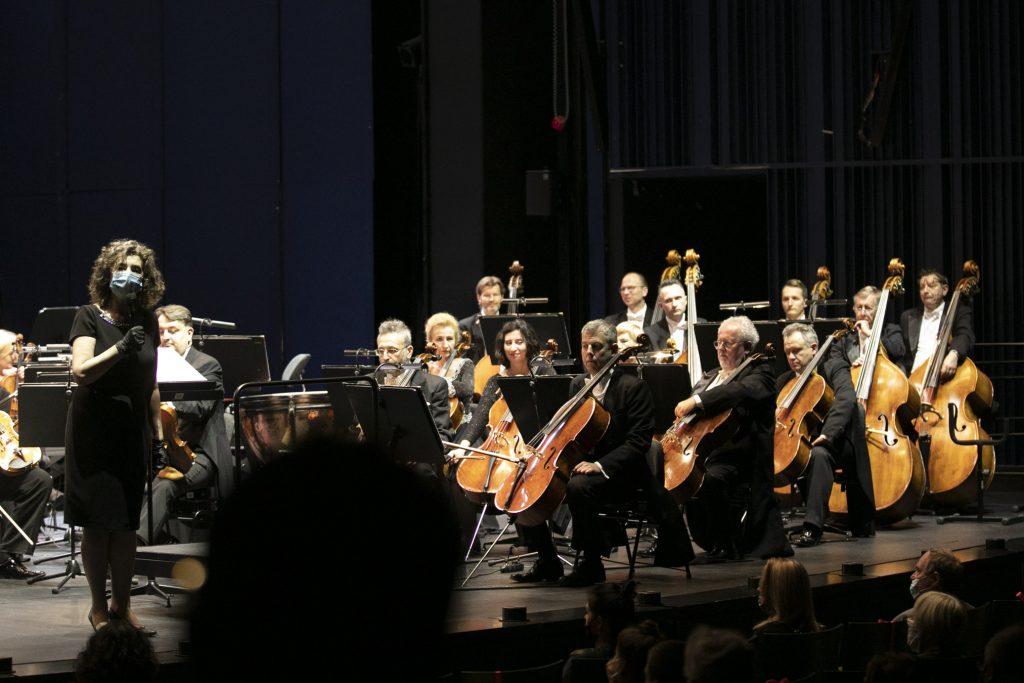 Po prawej stronie przy pulpitach siedzą muzycy - wiolonczeliści i kontrabasiści. Po lewej stronie, z mikrofonem, w maseczce ochronnej i rękawiczkach stoi Dyrektor Opery i Filharmonii Podlaskiej- Ewa Iżykowska Lipińska.