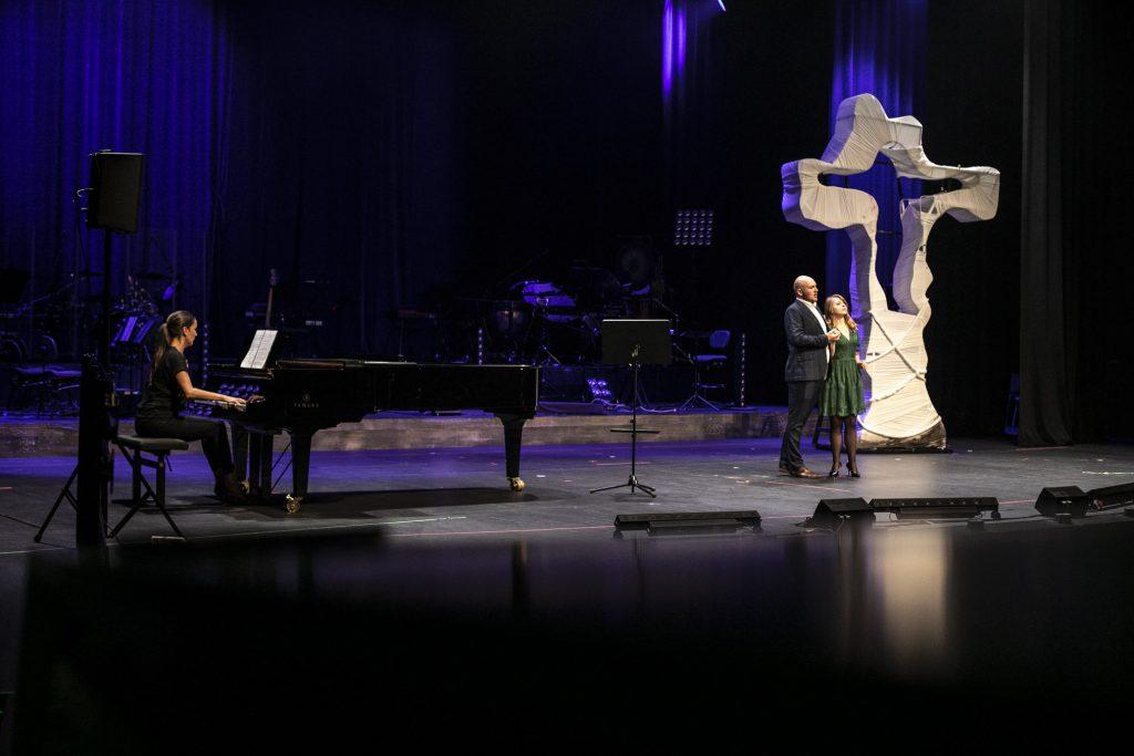 Przy fortepianie, po lewej stronie sceny, siedzi kobieta. Dalej stoi para trzymając się za ręce. Za nimi widać duży, biały krzyż.