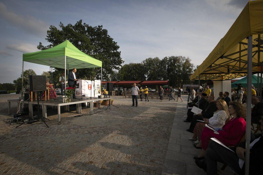 Plac w Supraślu. Po lewej stronie zadaszona scena, po prawej widownia wypełniona publicznością.