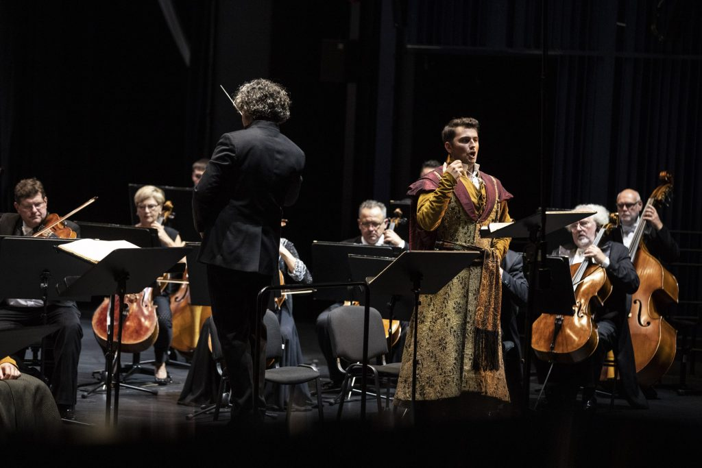 Na środku, tyłem stoi dyrygent. Po jego prawej stronie śpiewa solista w stroju szlacheckim. Za nimi siedzi grupa smyczkowa Orkiestry OiFP.
