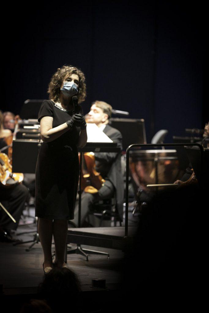 Z mikrofonem, w maseczce ochronnej i rękawiczkach, stoi Dyrektor Opery i Filharmonii Podlaskiej - Prof. Ewa Iżykowska - Lipińska. Dalej, przy pulpitach siedzą muzycy grupy smyczkowej.
