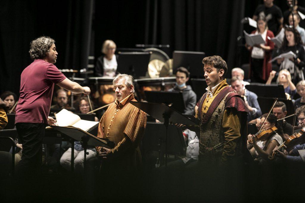 Po lewej stronie stoi dyrygent. Przed nim śpiewa dwóch mężczyzn w strojach szlacheckich. Za nimi gra orkiestra Opery. W oddali widać część chóru.
