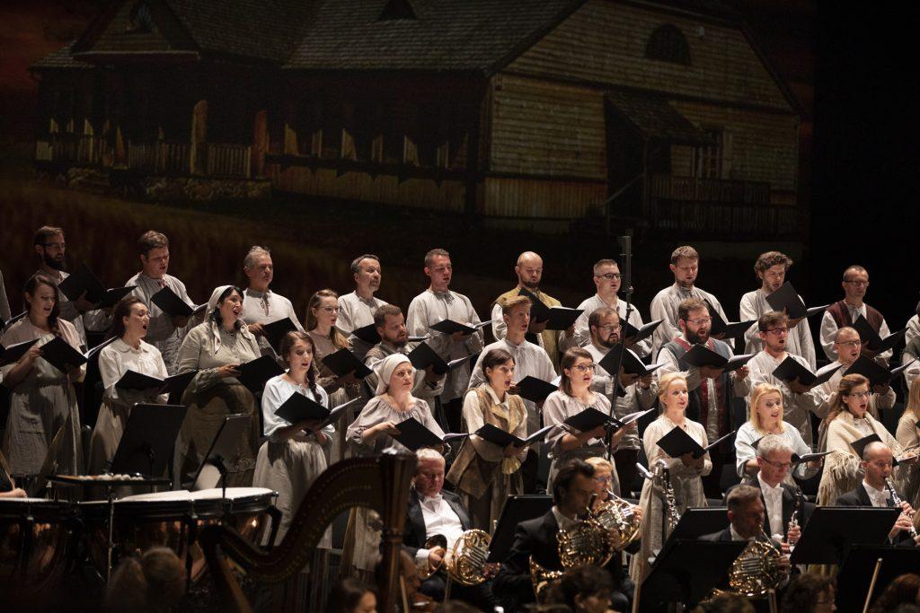 Zbliżenie na chór. Niej widoczna grupa dęta orkiestry , za nią stoi chór w białych strojach. Artyści chóru trzymają rozłożone nuty. Widok na tle scenografii przedstawiającej dwór szlachecki.
